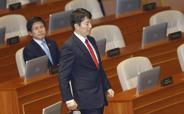 Lee Seok-Ki (R), lawmaker of opposition United Progressive Party, walks to deliver his speech as Justice Minister Hwang Kyo-ahn looks at him during a plenary session at parliament in Seoul September 4, 2013. REUTERS/Lee Jae-Won