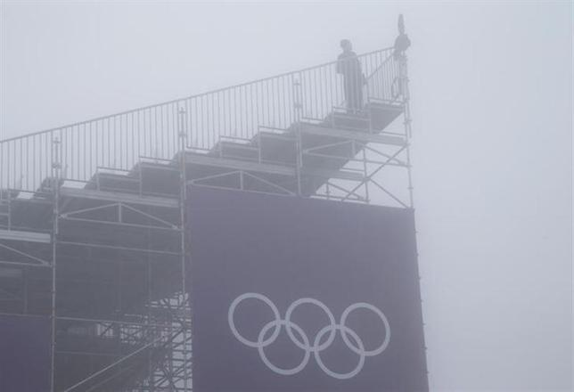A person looks on from a spectator stand amidst fog during a delayed start for the men's snowboard cross competition at the 2014 Sochi Winter Olympic Games in Rosa Khutor February 17, 2014. REUTERS/Mike Segar