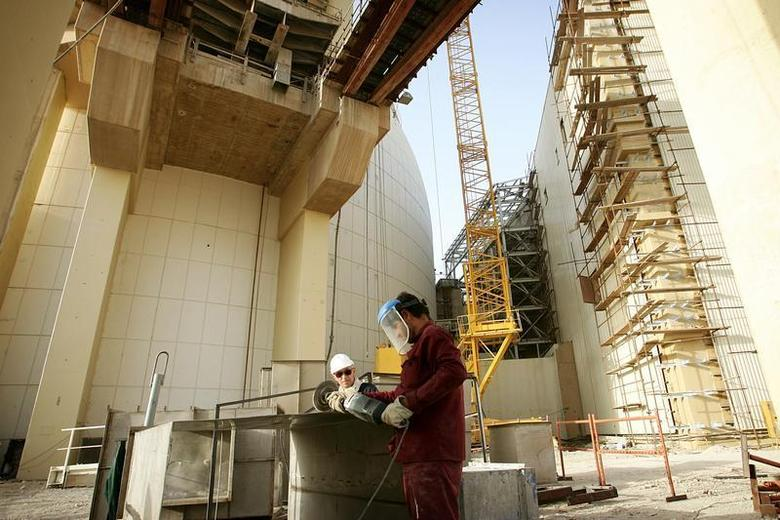 Workers work at the nuclear plant in the southwestern Iranian city of Bushehr June 22, 2005.