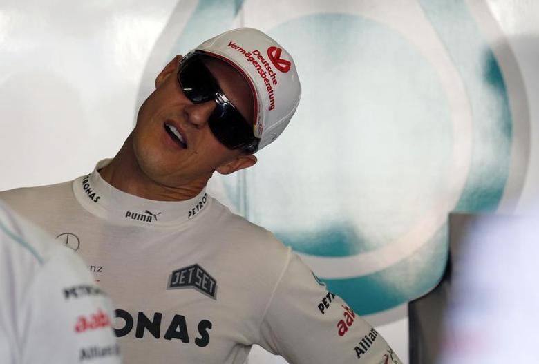 Mercedes Formula One driver Michael Schumacher of Germany stretches his neck inside his team garage during the second practice session of the Japanese F1 Grand Prix at the Suzuka circuit October 5, 2012. REUTERS/Kim Kyung-Hoon