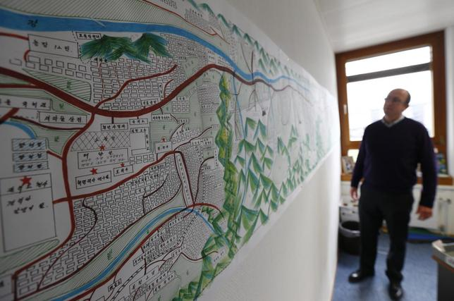 A United Nations Human Rights staff stands in front of a drawing illustrating North Korean labour camp no 18, a gift made in December 2012 by survivor Kim Hye Sook, in Geneva February 17, 2014. REUTERS/Denis Balibouse