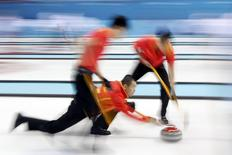 China's skip Liu Rui (C) delivers a shot during their men's curling round robin game against Britain at the Ice Cube Curling Center during the 2014 Sochi Winter Olympics February 17, 2014. REUTERS/Marko Djurica