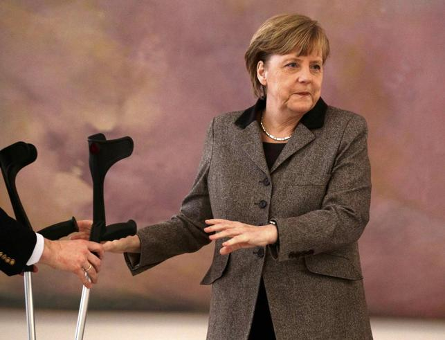 An aide take the crutches of German Chancellor Angela Merkel as she attends the appointment ceremony of the new Agriculture Minister Christian Schmidt (unseen) at Bellevue Castle in Berlin February 17, 2014. REUTERS/Tobias Schwarz