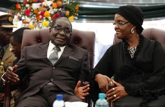 Zimbabwe President Robert Mugabe (L) speaks to his wife Grace during the funeral of his sister, Bridget, in the village of Zvimba, 90 km west of Harare January 21 2014. REUTERS/Philimon Bulawayo