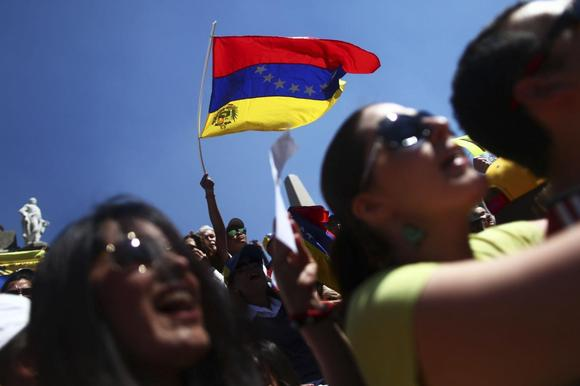 A Venezuelan opposition supporter waves a Venezuelan flag during a protest against Venezuelan President Nicolas Maduro's government at Angel de la Independencia monument in Mexico City, February 16, 2014. REUTERS/Edgard Garrido