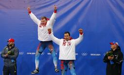 Russia's Alexander Zubkov (2nd L) and Alexey Voevoda (2nd R) celebrate on the podium at the flower ceremony between Switzerland's Alex Baumann (L) and Steven Holcomb of the U.S. after winning the two-man bobsleigh event at the 2014 Sochi Winter Olympics, at the Sanki Sliding Center in Rosa Khutor February 17, 2014. REUTERS/Arnd Wiegmann