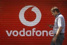 Un hombre revisa su teléfono celular mientras camina frente a una tienda que tiene el logo de Vodafone en Mumbái, 15 de enero de 2014. La compañía de telecomunicaciones británica Vodafone dijo que presentó el lunes una denuncia contra Telefónica ante la Comisión Nacional de los Mercados y la Competencia (CNMC) por infracción de normas de derecho español y de derecho comunitario de la competencia, que se refieren a conductas colusorias y al abuso de posición dominante. REUTERS/Danish Siddiqui