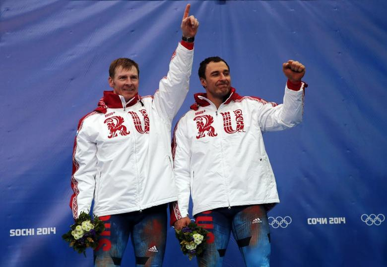 Russia's pilot Alexander Zubkov (L) and Alexey Voevoda celebrate on the podium at the flower ceremony after winning the men's two-man bobsleigh competition at the 2014 Sochi Winter Olympics February 17, 2014. REUTERS/Fabrizio Bensch