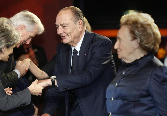 Former French President Jacques Chirac (C) shakes hands with guests as he arrives with his wife Bernadette to attend the award ceremony for the ''Prix de la Fondation Chirac'' at the Musee du Quai Branly in Paris November 21, 2013 file photo. REUTERS/Jacky Naegelen/Pool