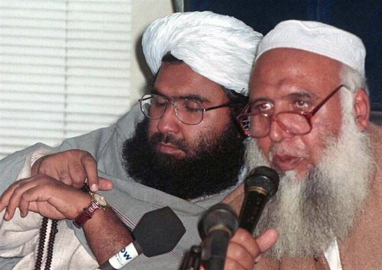 Pakistani cleric Maulana Masood Azhar (L) adjusts his watch during a news conference February 4. REUTERS/Files