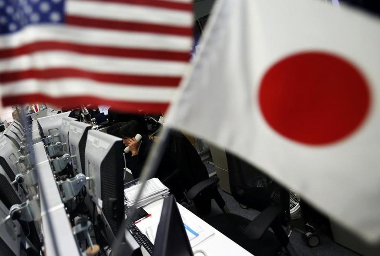 An employee of a foreign exchange trading company working is seen between the national flags of Japan and the U.S. in Tokyo January 6, 2014. REUTERS/Yuya Shino