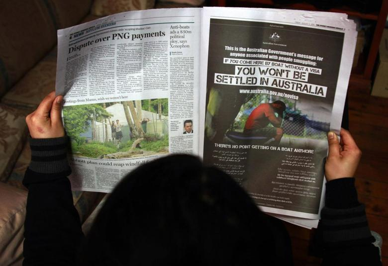 A woman reads a newspaper containing an advertisement (R) publicising the Australian government's new policy on asylum seekers arriving by boat, in Sydney in this August 2, 2013 file photo. REUTERS/David Gray/Files