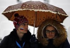 """Российские болельщики стоят под зонтом в ожидании начала первой попытки в женском гигантском слаломе в центре """"Роза Хутор"""" 18 февраля 2014 года. Во вторник на зимних Олимпийских играх в Сочи будут разыграны семь комплектов медалей. REUTERS/Kai Pfaffenbach"""