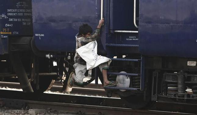A ragpicker boy jumps onto a moving train in search of plastic bottles for reselling, at a railway station in New Delhi February 18, 2014. REUTERS/Adnan Abidi