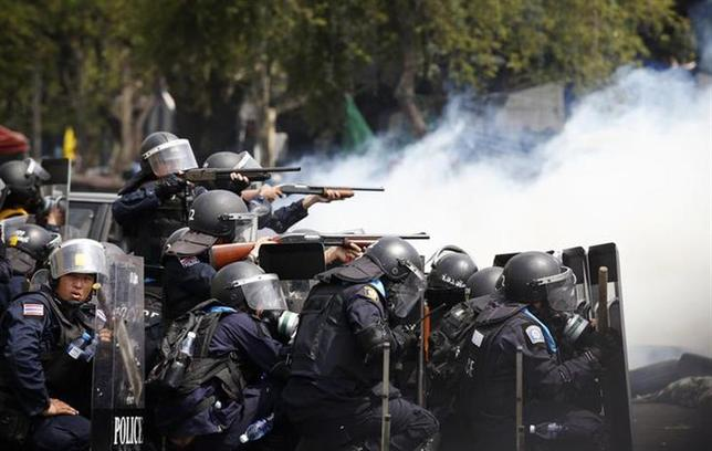 Thai policemen aim their weapons towards anti-government protesters during clashes near Government House in Bangkok February 18, 2014. REUTERS/Athit Perawongmetha