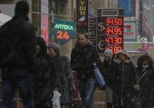 Люди проходят мимо пункта обмена валют в Москве 11 февраля 2014 года. Рубль умеренно подешевел к бивалютной корзине и её компонентам, оставаясь вблизи абсолютных минимумов, достигнутых в прошлую пятницу. REUTERS/Maxim Shemetov