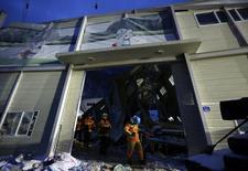 Спасатели выходят из обрушившегося здания в городе Кенджу 18 февраля 2014 года. Десять человек, пришедших на вечеринку по случаю зачисления новых студентов, погибли из-за обрушения здания на южнокорейском горном курорте, сообщили представители службы чрезвычайных происшествий. REUTERS/Kim Hong-Ji