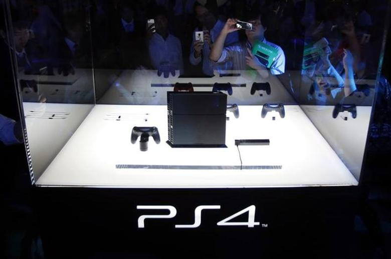 Visitors take pictures of Sony Corp's PlayStation 4 new game console at the Tokyo Game Show in Chiba, east of Tokyo, September 19, 2013. REUTERS/Yuya Shino/Files