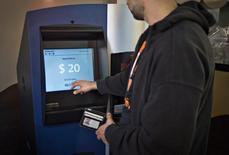Человек пользуется первым биткоин-банкоматом в Ванкувере, Канада 29 октября 2013 года. Компания Robocoin сообщила, что установит в конце этого месяца первый в США банкомат, с помощью которого можно будет покупать и продавать биткоины. REUTERS/Andy Clark
