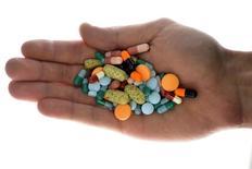 Человек держит в руках различные лекарства в Любляне 18 сентября 2013 года. Крупнейший российский производитель лекарств Фармстандарт увеличил выручку в 2013 году на 8,8 процента до 55,9 миллиарда рублей, сообщила компания во вторник. REUTERS/Srdjan Zivulovic