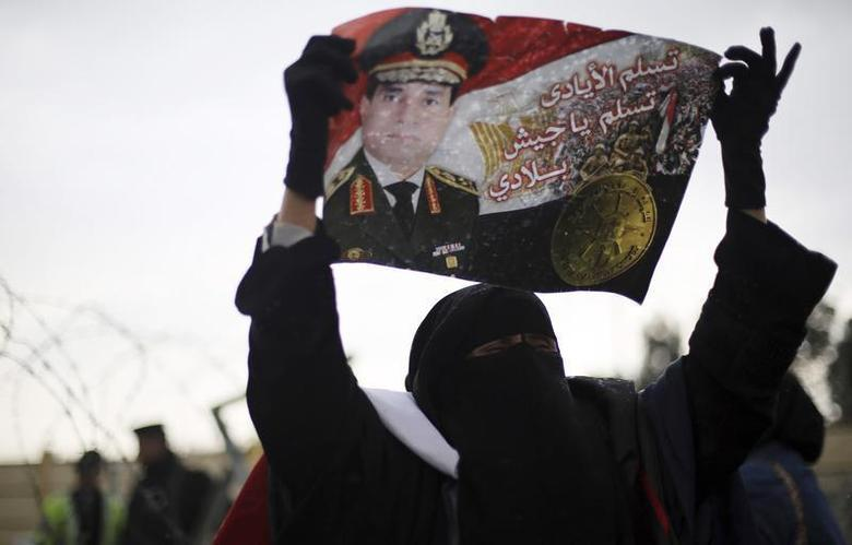 A supporter of Egypt's army chief Field Marshal Abdel Fattah al-Sisi shout slogans while holding a poster of him outside a police academy, where the trial of ousted Egyptian President Mohamed Mursi and members of the Muslim Brotherhood is due to take place, on the outskirts of Cairo, February 16, 2014. REUTERS/Amr Abdallah Dalsh