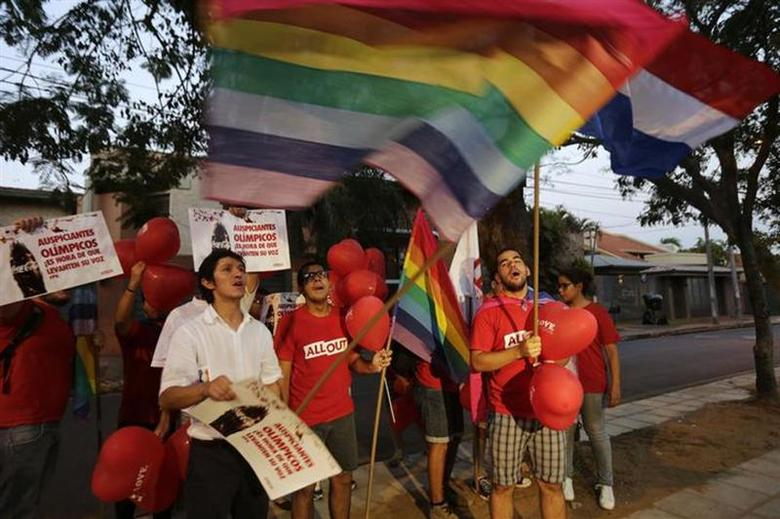 Members of Paraguay's LGBT community hold placards and rainbow flags as they protest outside the Russian embassy in Asuncion against Russia's anti-gay laws, ahead of the Sochi 2014 Olympics, February 5, 2014. REUTERS/Jorge Adorno