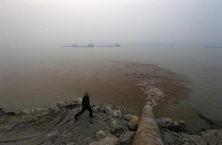 A man walks by a pipe discharging waste water into the Yangtze River from a paper mill in Anqing, Anhui province, December 4, 2013. REUTERS/William Hong