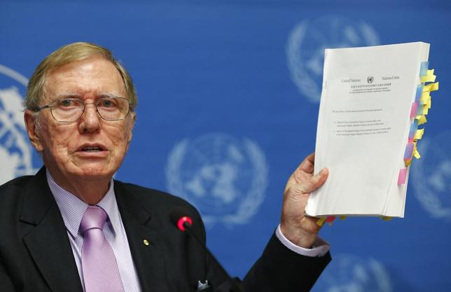 Michael Kirby, Chairperson of the Commission of Inquiry on Human Rights in North Korea holds a copy of his report during a news conference at the United Nations in Geneva February 17, 2014. REUTERS/Denis Balibouse