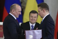 Главы Нафтогаза и Газпрома под наблюдением президента Украины Виктора Януковича (в центре) обмениваются подписанными документами после переговоров в Кремле 17 декабря 2013 года. Высокопоставленный источник в правительстве Украины сказал Рейтер, что госкомпания Нафтогаз заплатила $1,282 миллиарда за российский газ, импортированный в 2013 году, в результате чего снизила долг перед Газпромом до $1,470 миллиарда. REUTERS/Sergei Karpukhin
