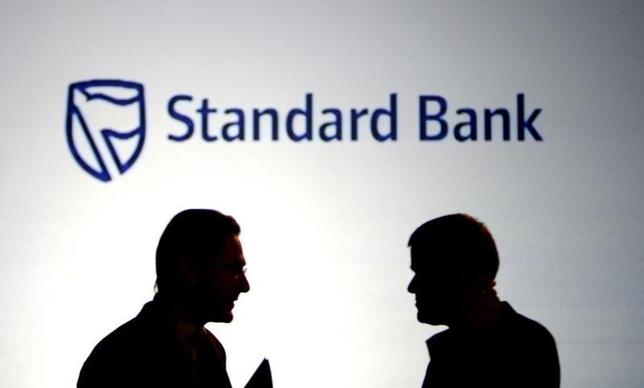 Businessmen chat in front of a Standard Bank logo in Sandton outside Johannesburg October 25, 2007. REUTERS/Siphiwe Sibeko