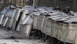 Бойцы внутренних войск прикрываются щитами в столкновениях с протестующими в Киеве 18 февраля 2014 года. Силовые структуры Украины пошли в наступление на киевский майдан, не дожидаясь истечения срока собственного ультиматума, которым они дали протестующим два часа, чтобы очистить улицы столицы, где во вторник возобновились кровопролитные столкновения после трёх недель перемирия. REUTERS/Vlad Sodel