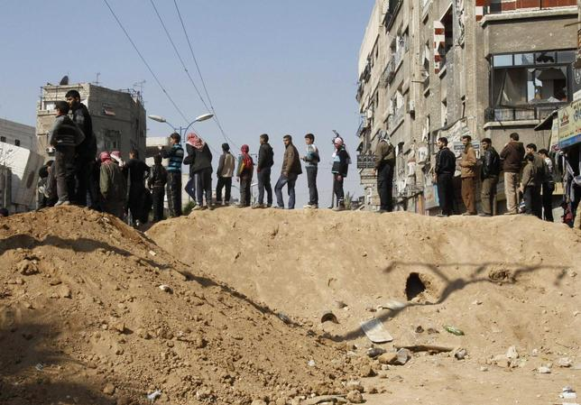 Syrian civilians are seen in Babila town, southeast Damascus February 17, 2014, after a local ceasefire agreement was reached. REUTERS/Khaled al-Hariri