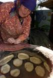 Мариам Камалденова из Казахстана заглядывает в тандыр с лепешками в своем доме в селении Прямой Путь под Алма-Атой 11 августа 2003 года. Экспортёр зерна Казахстан направит на внутренний рынок 509.000 тонн зерна по фиксированной цене, чтобы помешать росту цены на хлеб после резкой девальвации тенге, которая отозвалась уличным протестом. REUTERS/Shamil Zhumatov