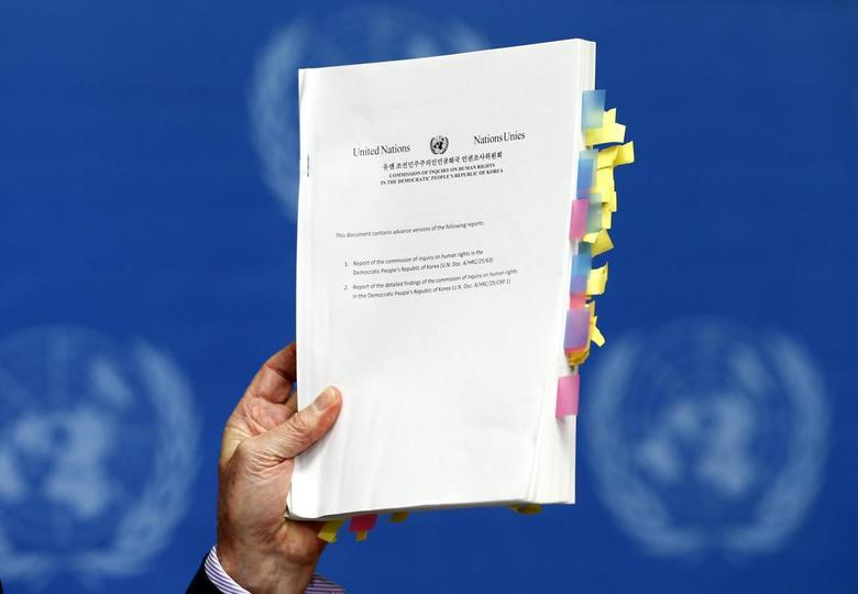 Michael Kirby, Chairperson of the Commission of Inquiry on Human Rights in North Korea, holds a copy of his report during a news conference at the United Nations in Geneva February 17, 2014. REUTERS/Denis Balibouse
