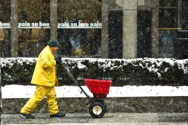 A man throws salt on a street during the arrival of a snowstorm in Exchange Place, New Jersey, December 10, 2013. REUTERS/Eduardo Munoz
