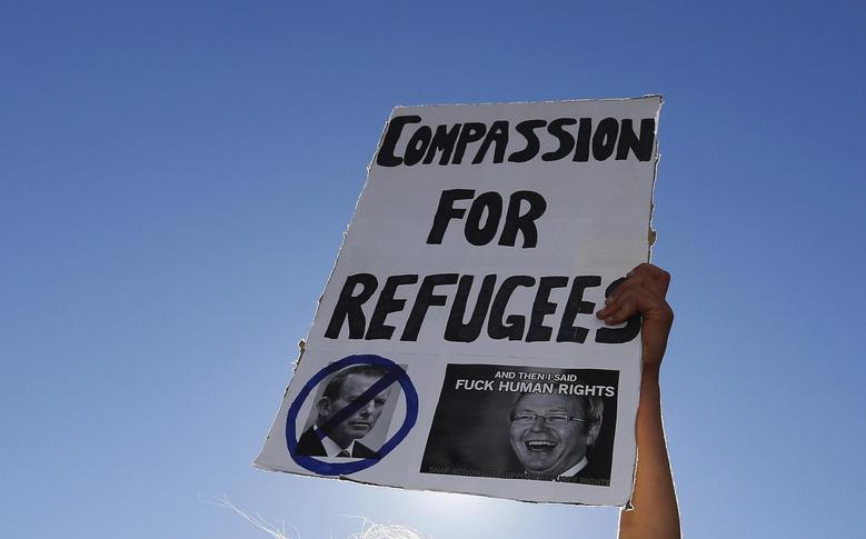 A woman holds a banner during a rally in support of asylum seekers, in central Sydney in this August 10, 2013 file photo. To match Insight AUSTRALIA-NAURU/ REUTERS/Daniel Munoz