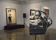 "Paintings titled ""Crazy Horse Car Door"" and in the background, ""Kissing Coppers"", by the British street artist Banksy, are seen on display at LMNT Gallery in Miami, Florida February 18, 2014. REUTERS/Zachary Fagenson"
