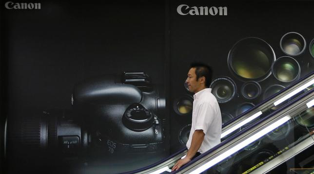 A man takes a downward escalator in front of an advertisement of Canon digital cameras at an electronics retail store in Tokyo July 24, 2013. REUTERS/Issei Kato