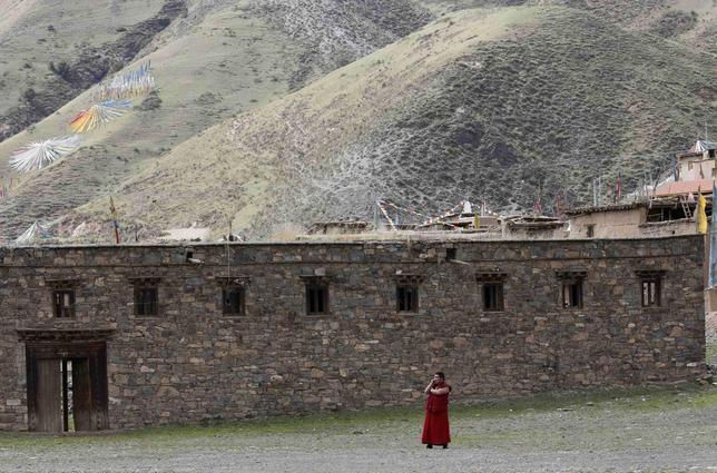 A Tibetan monk uses a mobile phone near the Dzamthang Jonang monastery in Barma township May 16, 2013. REUTERS/Kim Kyung-Hoon
