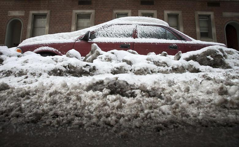 A car that is completely inundated by snow and ice that have accumulated from recent storms is pictured in the Manhattan borough of New York February 16, 2014. REUTERS/Carlo Allegri