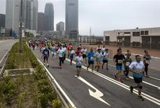 Participants run past Two International Finance Centre (IFC), as they compete in the Hong Kong marathon February 16, 2014. REUTERS/Tyrone Siu
