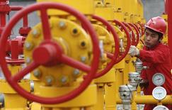 Рабочий крутит вентиль на нефтяном месторождении близ города Гуанъань в провинции Сычуань 7 декабря 2007 года. Россия и Ирак наращивают поставки нефти в Китай, где спрос на топливо растет все медленнее, отвоевывая рынок у поставщиков из Латинской Америки и Африки, что создает предпосылки для снижения цены на нефтяные эталоны. REUTERS/Stringer