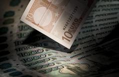 Купюры валют евро и рубль в Москве 17 февраля 2014 года. Рубль в среду утром несколько раз обновлял исторические минимумы к евро и бивалютной корзине за счет массового закрытия коротких валютных позиций после объявленного накануне решения Минфина покупать валюту для резервного фонда на рынке. REUTERS/Maxim Shemetov