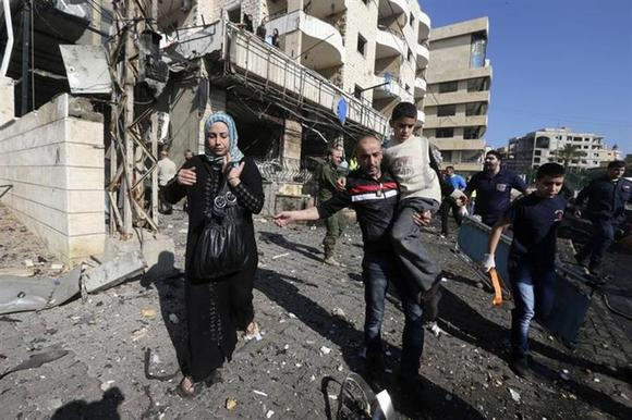 Civilians leave as rescuers rush to the site of an explosion in the southern suburbs of Beirut February 19, 2014. REUTERS/Hasan Shaaban