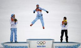 Winner Norway's Joergen Graabak (C), jumps on the podium applauded by second-placed and compatriot Magnus Hovdal Moan (L) and third-placed Germany's Fabian Riessle, during the flower ceremony for the Nordic Combined individual Gundersen 10 km event of the Sochi 2014 Winter Olympic Games, at the RusSki Gorki Ski Jumping Center in Rosa Khutor, February 18, 2014. REUTERS/Kai Pfaffenbach