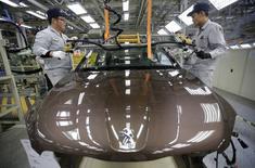 Работники на заводе Dongfeng Peugeot Citroen Automobile в Ухане 13 февраля 2014 года. Убыточный французский автопроизводитель PSA Peugeot Citroen получил шанс начать новую жизнь, после того китайская госкомпания Dongfeng согласилась присоединиться к французскому правительству и нынешним владельцам Peugeot и вложить на троих 3 миллиарда евро. REUTERS/Stringer