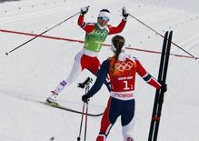 Норвежские лыжницы Игвильд Флугстад Эстберг и Марит Бьерген (лицом к фотографу) после победы в лыжном командном спринте классическим стилем на Олимпиаде в Сочи 19 февраля 2014 года. Сборная Норвегии выиграла лыжный командный спринт классическим стилем на Олимпиаде в Сочи, команда России пришла к финишу шестой. REUTERS/Stefan Wermuth