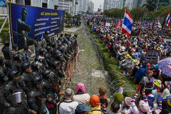 Anti-government protesters gather as Thai soldiers stand guard at a Defence Ministry compound serving as a temporary office for Thai Prime Minister Yingluck Shinawatra in north Bangkok February 19, 2014. REUTERS/Athit Perawongmetha