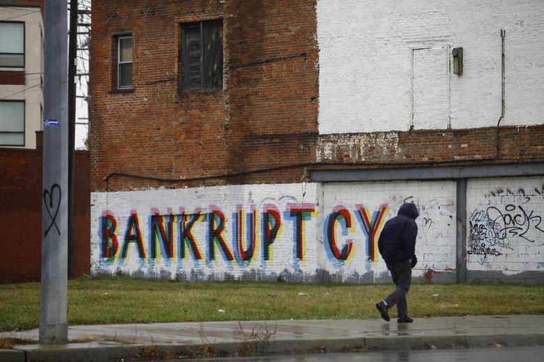A man walk past graffiti in Detroit, Michigan, December 3, 2013. REUTERS/Joshua Lott
