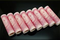 Billetes de 100 yuanes enrrollados para una ilustración fotográfica en Pekín, nov 5 2013. China ampliará la banda de cotización del yuan de una manera ordenada y acelerará la convertibilidad en la cuenta de capital, dijo el miércoles el banco central. REUTERS/Jason Lee